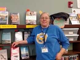 Chris Conrad, Fort Lewis Mesa Librarian, against book shelf