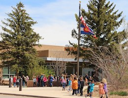 Students entering Ft. Lewis Mesa Elementary School and Library, and US flag
