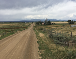 Dirt road heading north into distance mountains and clouds