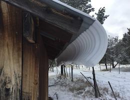 snow sliding off tin roof